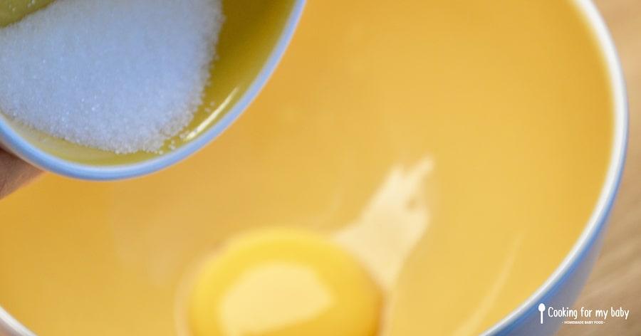 Mélanger le sucre et le jaune d'oeuf pour les biscuits à la cuillère de bébé